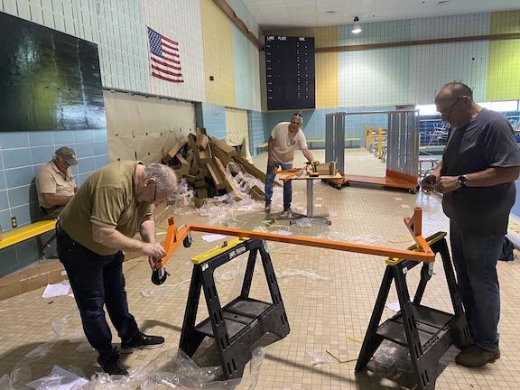 Rotarians help assemble costume racks